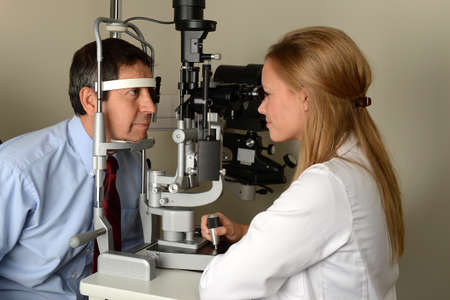 vision test: Doctor joven de ojos con su paciente durante un examen