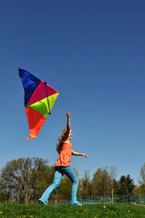 Young girl running with colorful kite against a blue sky photo