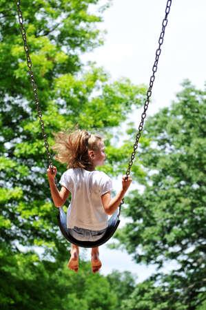 Jong Meisje op een schommel met bomen op de achtergrond Stockfoto