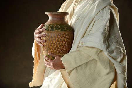 jesuschrist: Jesus Holdind a jug of water on a dark background
