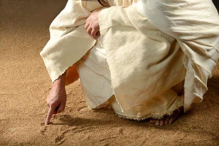 그의 손가락으로 모래에 예수 쓰기