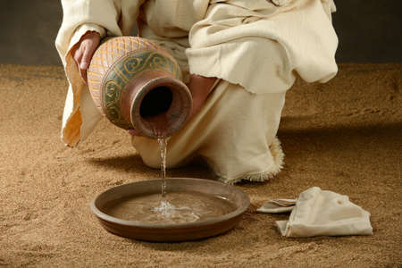 jesus hands: Jesus with a jug of water and a towell on a neatral background Stock Photo