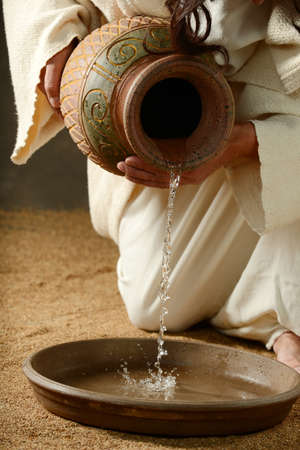 religious: Detail of Jesus pouring water on a neutral background Stock Photo