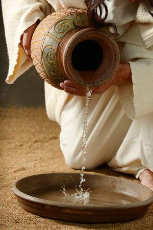 Detail van Jezus gieten water op een neutrale achtergrond Stockfoto