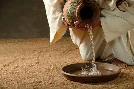 manos y pies: Jesús verter agua de una jarra (con copyspace para el texto) Foto de archivo