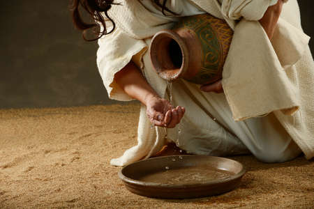 holy jug: Jesus pouring water from a jug  Stock Photo