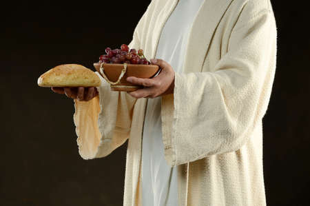 jesus easter: Jesus holding a bread and grapes as a metaphor                            Stock Photo