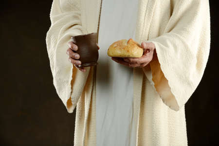 jesus hands: Jesus holding bread and a cup of wine as a methaphore Stock Photo