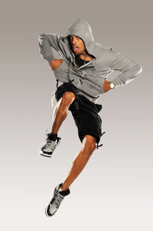 aerobica: Hip Hop Dancer jumping wearing shorts and tennis shoes on a neutral background Stock Photo