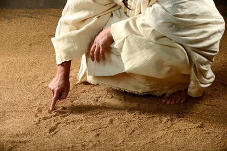 mano de dios: Jesús Escritura en la arena con su dedo