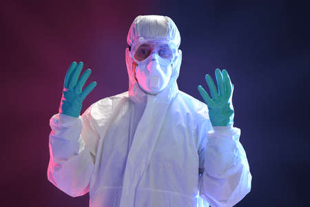 protective suit: Scientist in full protective hazmat suit with dramatic lighting as background