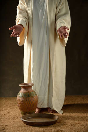 Jesus standing with a jar of water and a bowl Stock Photo