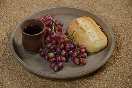 Still life with grapes, wine and bread on a tray against a sandy background