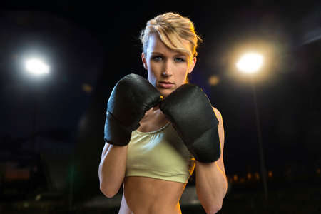 Young boxer woman at night with lights on Stock Photo