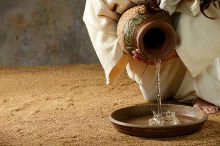 Jezus giet water uit een pot voor de voeten wassen