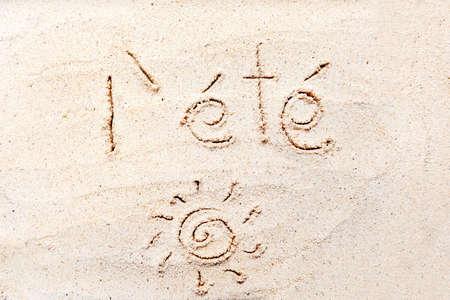 """Handwriting words """"l été"""" on sand of beach"""