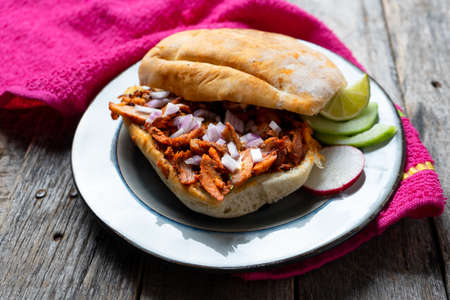 """Mexican food: pork sandwich also known as """"torta al pastor"""" on wooden background"""