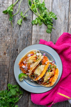Mexican food: Authentic tacos al pastor with lime and pineapple on wooden background Standard-Bild