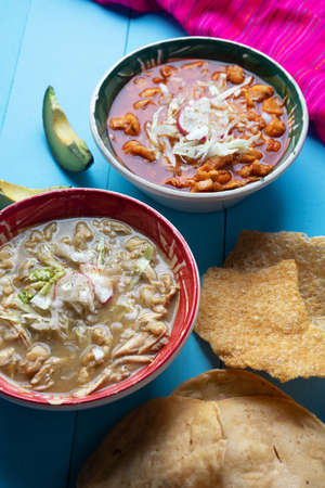 Traditional mexican red and green pozole soup on blue background