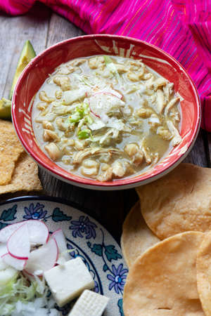 Traditional mexican green pozole soup on wooden background