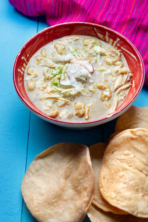 Traditional mexican green pozole soup on blue background