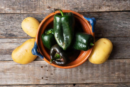 Raw potatoes and poblano peppers on wooden background