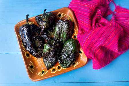 Roasted poblano peppers ready to be peeled in clay plate on colorful backgrounds