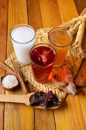 """Set of traditional Mexican fresh water also called """"Aguas Frescas"""". Hibiscus, tamarind and horchata on wooden background"""
