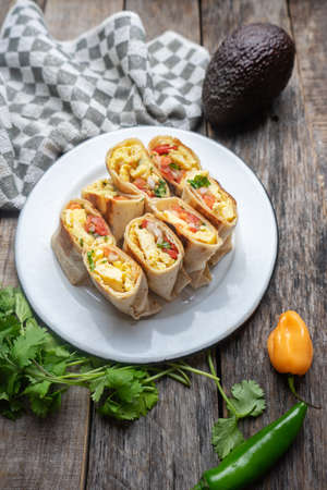 Traditional mexican egg burritos with fresh sauce on wooden background