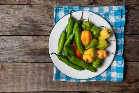Raw serrano and habanero peppers on rustic wooden background