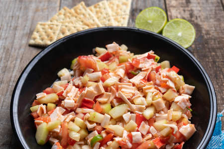 Traditional surimi crab ceviche with cucumber and tomato on wooden background Stock Photo