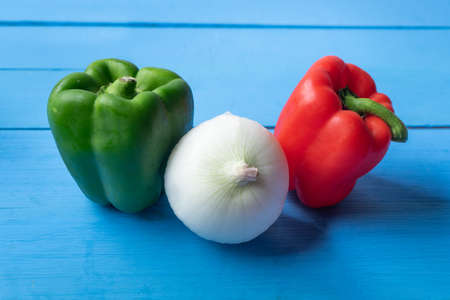 Green and red bell peppers with white onion on blue background