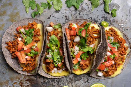 """Traditional mexican quesadillas with shredded pork also called """"chilorio"""" on rustic background"""