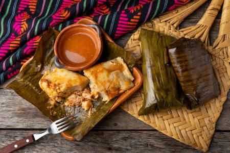 "Traditional mexican tamales wrapped in banana leaves also called ""oaxaqueños"" on wooden background"