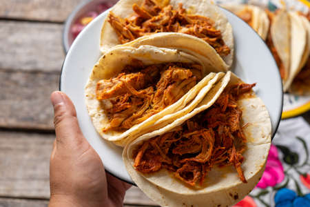 Traditional mexican cochinita pibil tacos with habanero sauce on wooden background