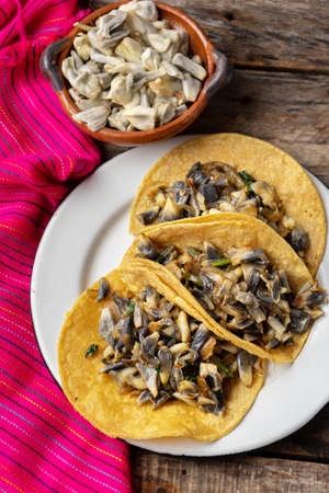 "Traditional mexican corn smut taco called ""huitlacoche"" on wooden background"