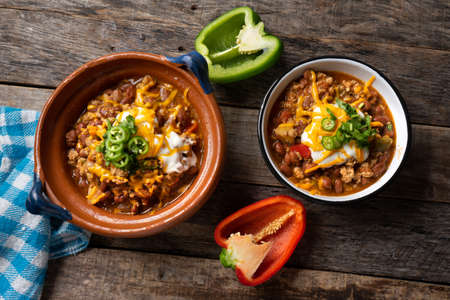 """Traditional texmex dish called """"Chili con carne"""" with cheese and sour cream on wooden background"""