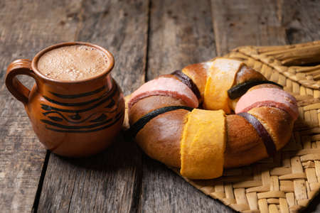 "Traditional King's day cake also called ""rosca"" with hot chocolate on wooden background"