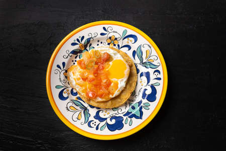 """Traditional mexican egg mounted on corn tortilla with sauce also called """"rancheros"""" on dark background"""