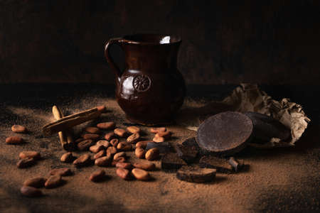 Traditional cacao beans and chocolate on dark background