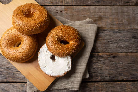 Traditional sesame bagels with spreadable cream cheese on wooden background