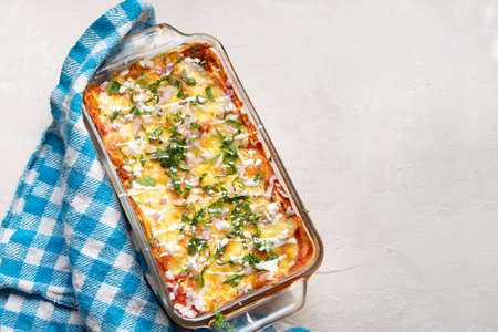 Traditional mexican red baked enchiladas with melted cheese and sour cream on white background