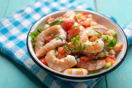 Traditional mexican shrimp ceviche with tomato and serrano pepper on turquoise background