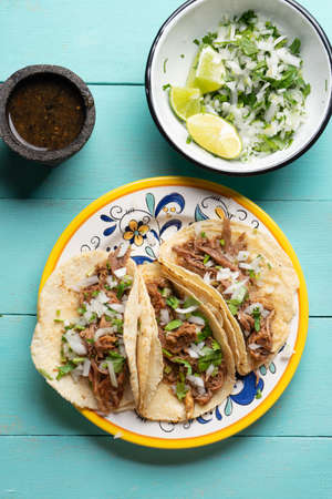 Traditional mexican slow cooked lamb tacos also called barbecue on turquoise background