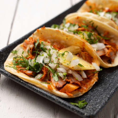 """Traditional mexican pork tacos called """"Al pastor"""" with pineapple on white background Standard-Bild"""