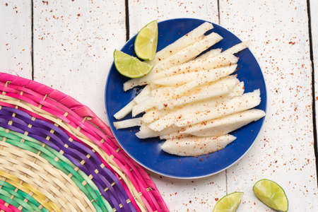 Traditional mexican jicama cutted with chili powder on white background Imagens