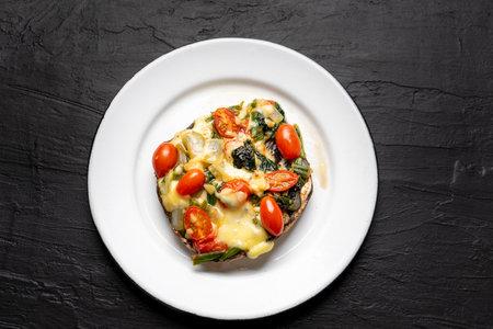 Portobello mushroom stuffed with spinach and cheese on dark background