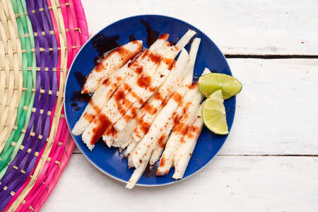 Traditional mexican jicama cutted with chili powder and piquant sauce on white background