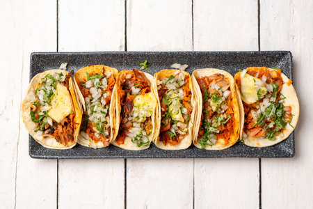 """Traditional mexican pork tacos called """"Al pastor"""" with pineapple on white background"""