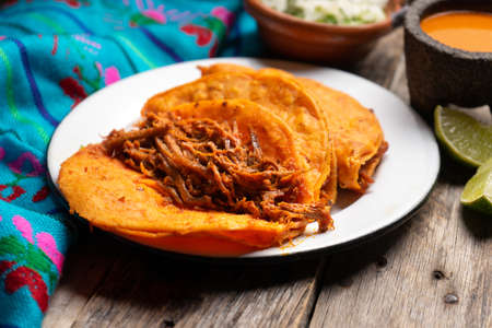 Traditional mexican beef birria tacos on wooden background